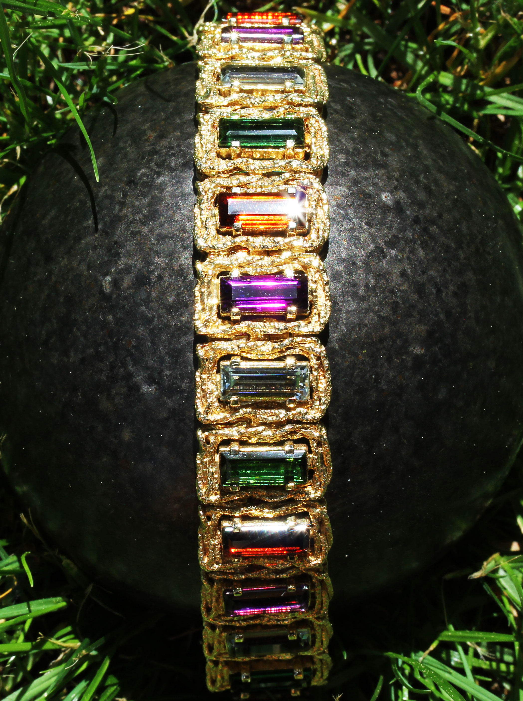 Gold bracelet with several gem stones