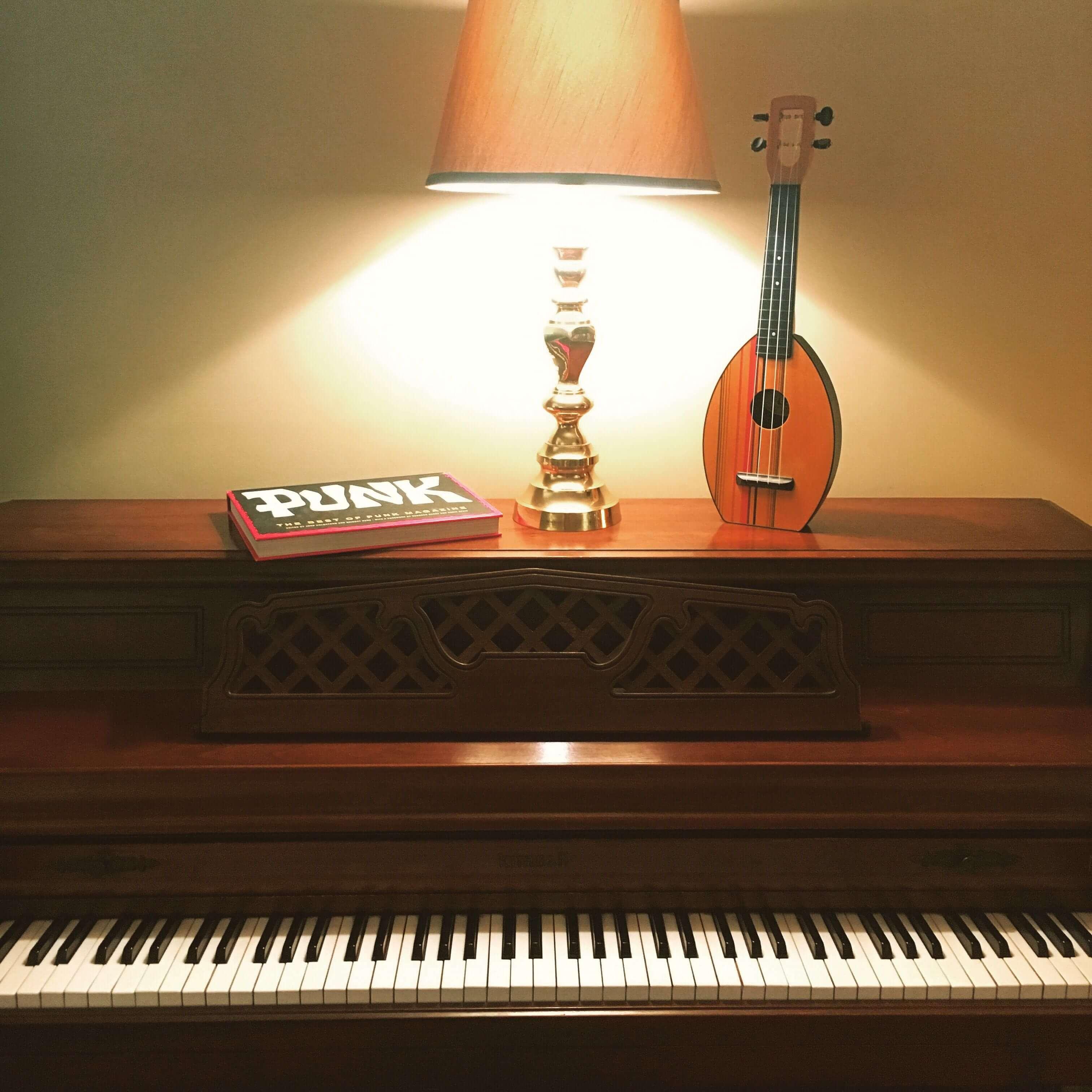 Kimball upright piano with uke in a rehearsal pod