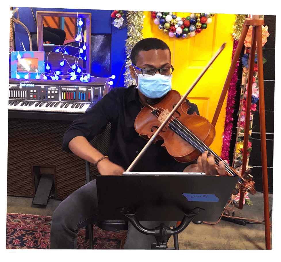 A violinist performs while wearing a face covering