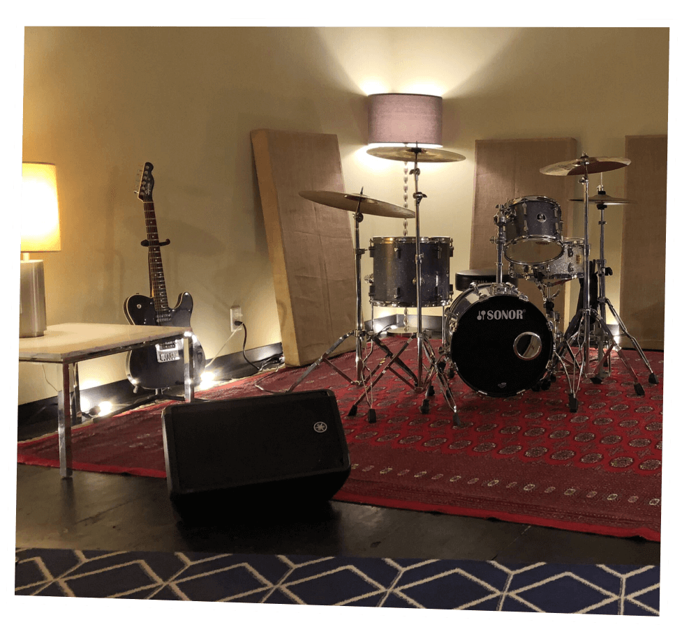 Interior of a rehearsal pod with a drum set, guitar, colorful rugs and dim lighting to set the mood.