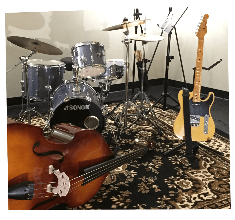 Interior of a pod with double bass, drum set, and a G&L telecaster-style guitar