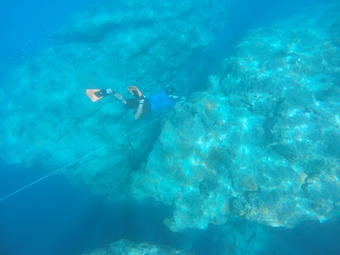Underwater, a man wearing a snorkel, fins, and mask swims down to a coral reef with an instrument tied to a tether.