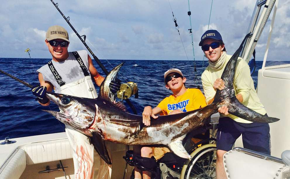 Logan Prickett, center, flanked by mate Colby Mason, left, and Captain Nick Stanczyk, right, show off a 105-pound swordfish that Prickett caught off the Florida Keys using an electric-assist fishing reel. Associated Press (2004)