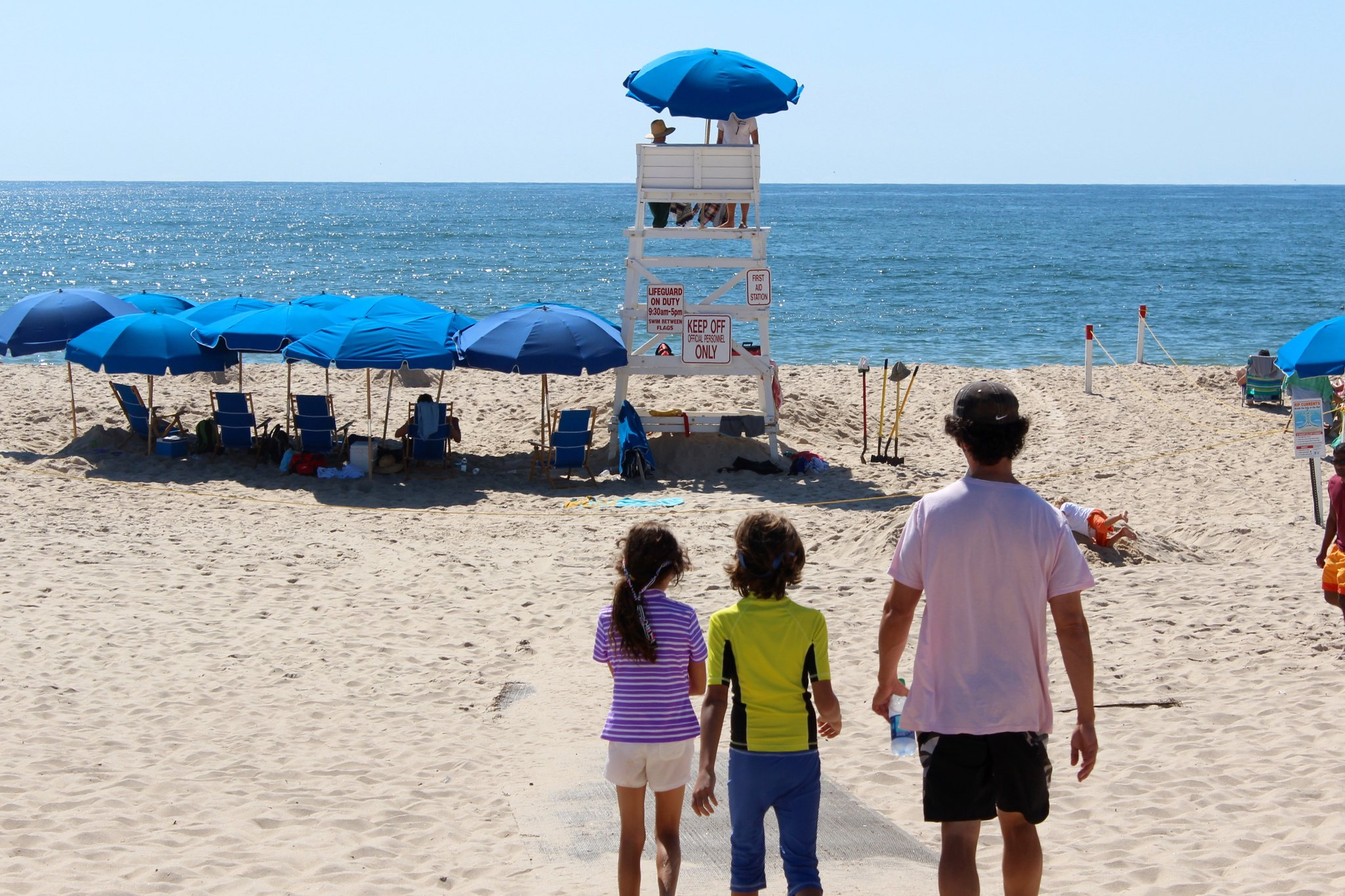 Two children and a man look out at the ocean and a life guard's hut