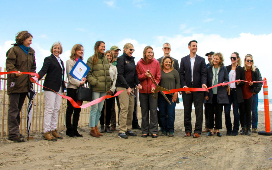 Encinitas Mayor Catherine Blakespear (center) cuts the ribbon for the Cardiff State Beach Living Shoreline project's opening May 22. Encinitas City Councilman Joe Mosca (standing third to the right from Blakespear) was among the various local, regional and state officials on hand for the event. (Nature Collective photo)