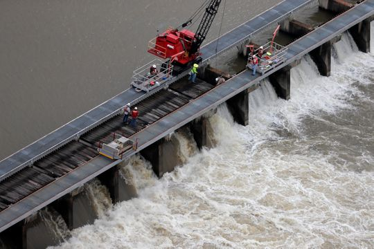 Workers open bays of the Bonnet Carre Spillway, to divert rising water from the Mississippi River to Lake Pontchartrain, upriver from New Orleans, in Norco, La., May 10. Freshwater from the diversion eventually makes its way to the Mississippi Coast, affecting marine life.