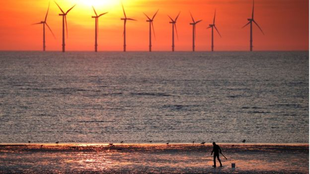 Several wind turbines are shown in the distance with a man on a beach in the near ground.