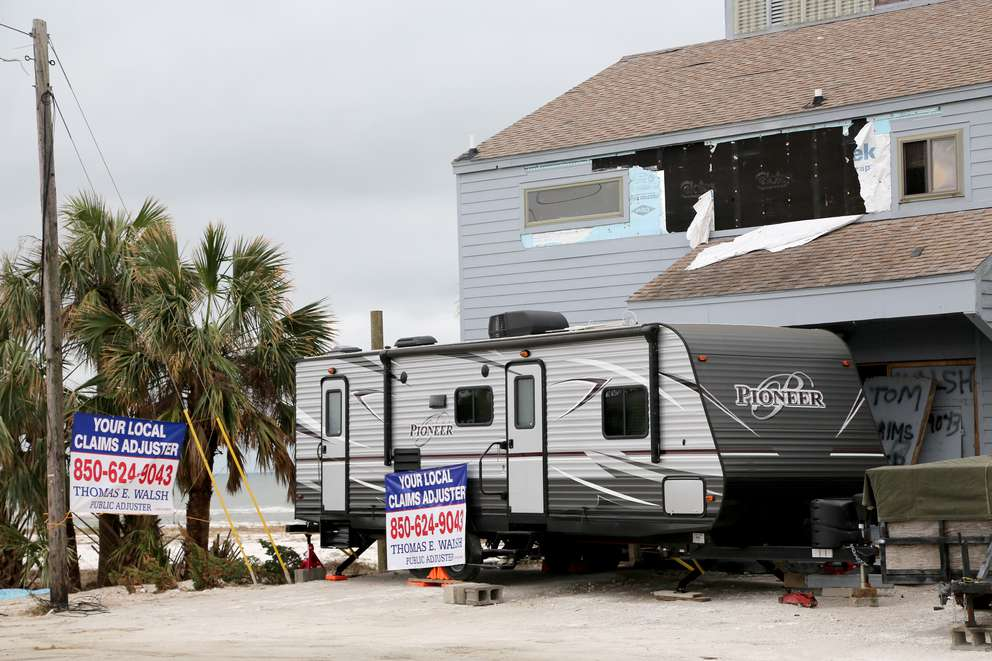 Signs advertise a local claims adjuster near Mexico Beach. DOUGLAS R. CLIFFORD   Times (2018)