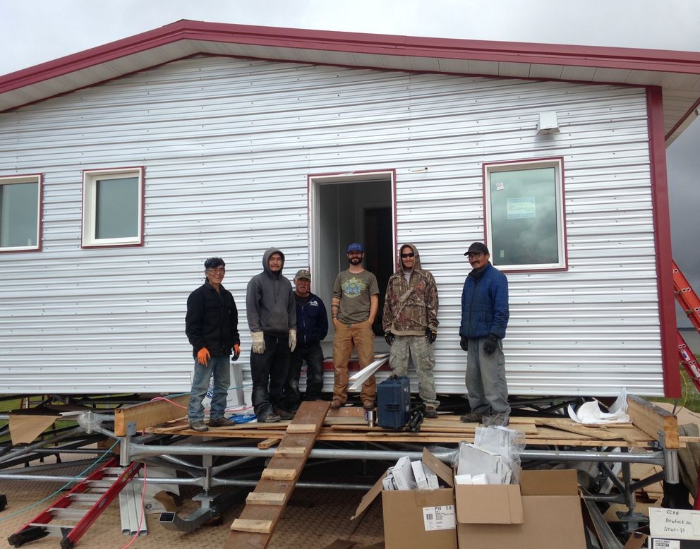 Aaron Cooke, in T-shirt and blue hat, in front of an efficient house he helped design after he and Newtok residents built it at the new village site of Mertarvik in 2016. (Photo by Molly Rettig)
