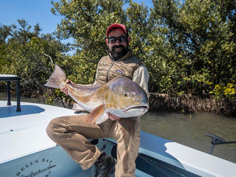 andrew mckean holding giant bull redfish