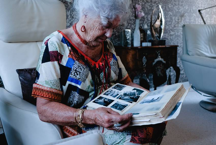 Mina Verton looks through a scrapbook of family photos at her home in Zierikzee.