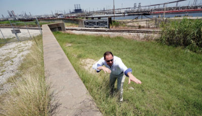 Engineer Steve Sherrill of the U.S. Army Corps of Engineers shows how much height is being added to seawalls and levees near a refinery in Port Arthur, Texas, in July 2018.