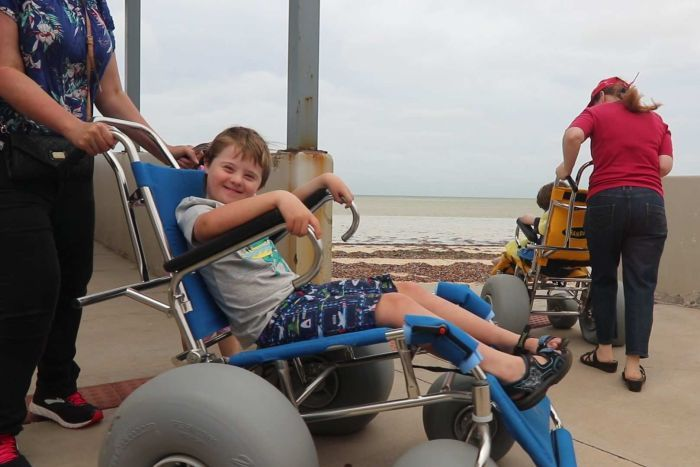 little boy smiling in wheelchair on left, wheelchair on the right
