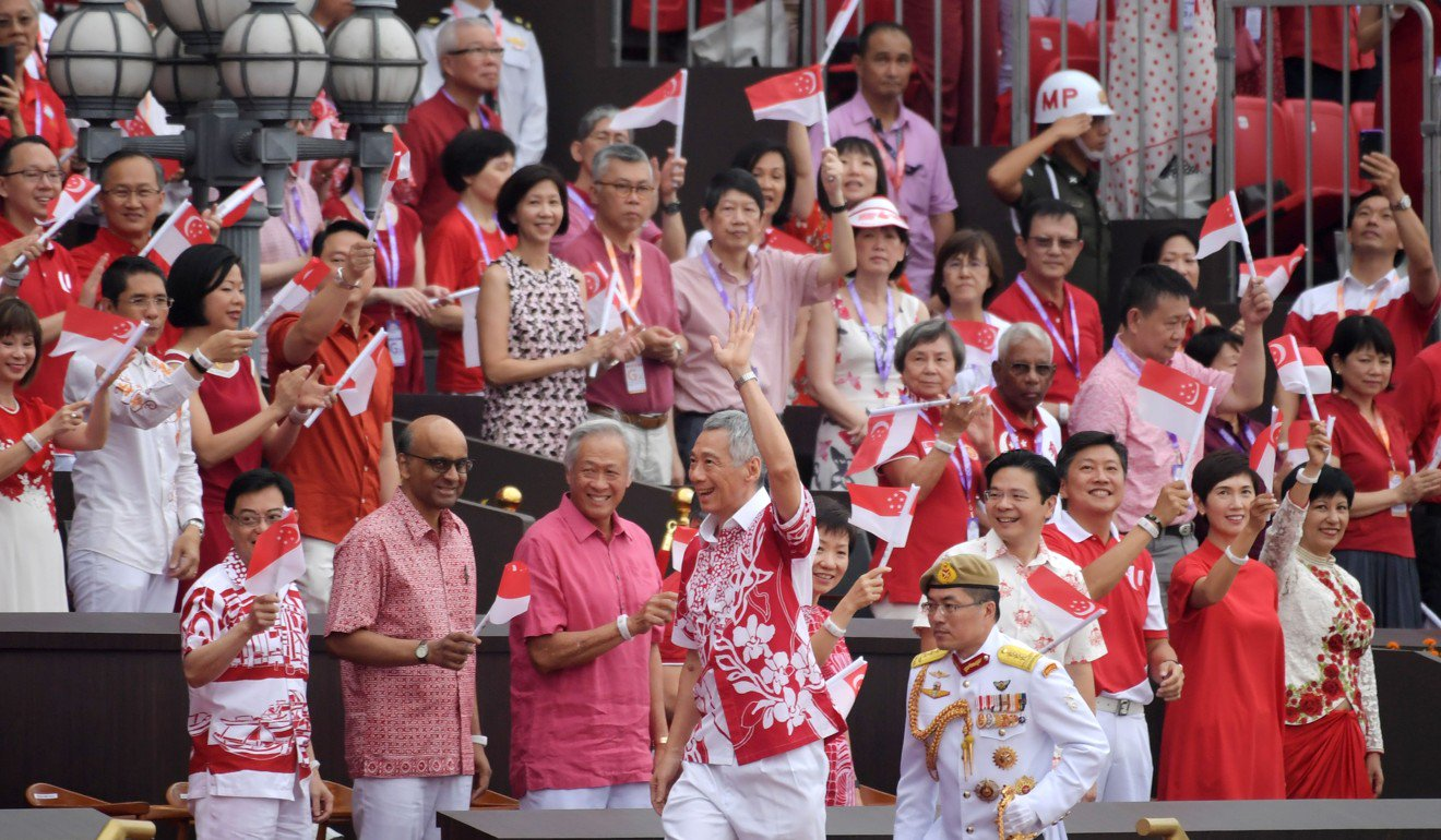 Prime Minister Lee Hsien Loong (front C) waves as he arrives for the 54th National Day Parade in Singapore. Photo: AFP