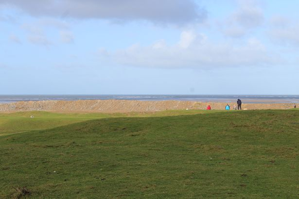 Golfers playing on Royal North Devon Golf Club's 9th hole with the new wall in the background.