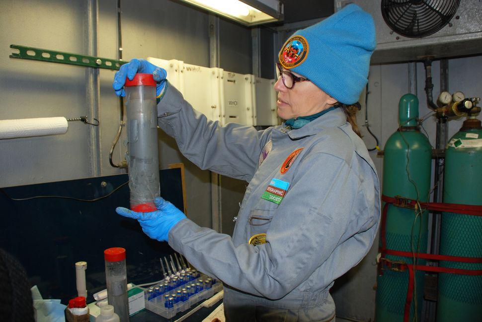 Samantha Joye inspects a core of marine sediment aboard Atlantis.