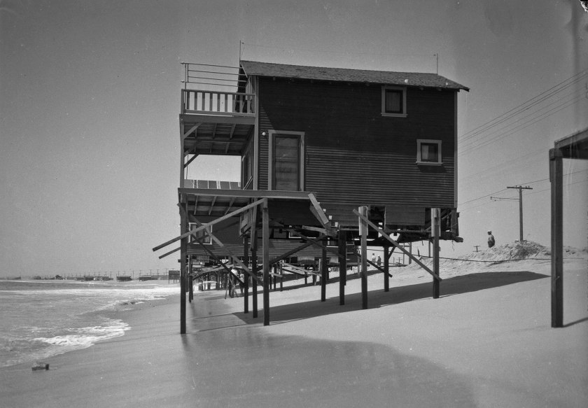 A beach house on stilts at water's edge at Newport Beach.