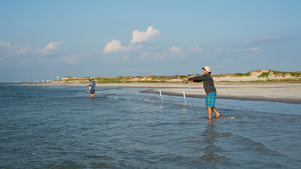 Jason Bologna, visiting from Pittsburgh, throws a line out while fishing along the shoreline of the southern point of Topsail Island Tuesday evening. (Port City Daily photo/Mark Darrough)