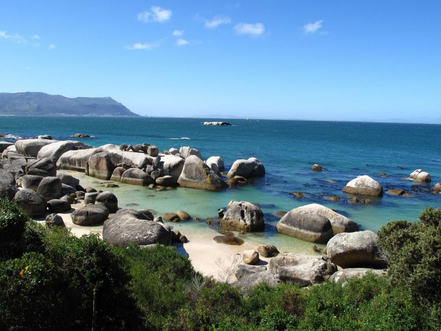 Half-submerged rocks are spread across a seashore, with a mountain in the background and a clear, blue sky.