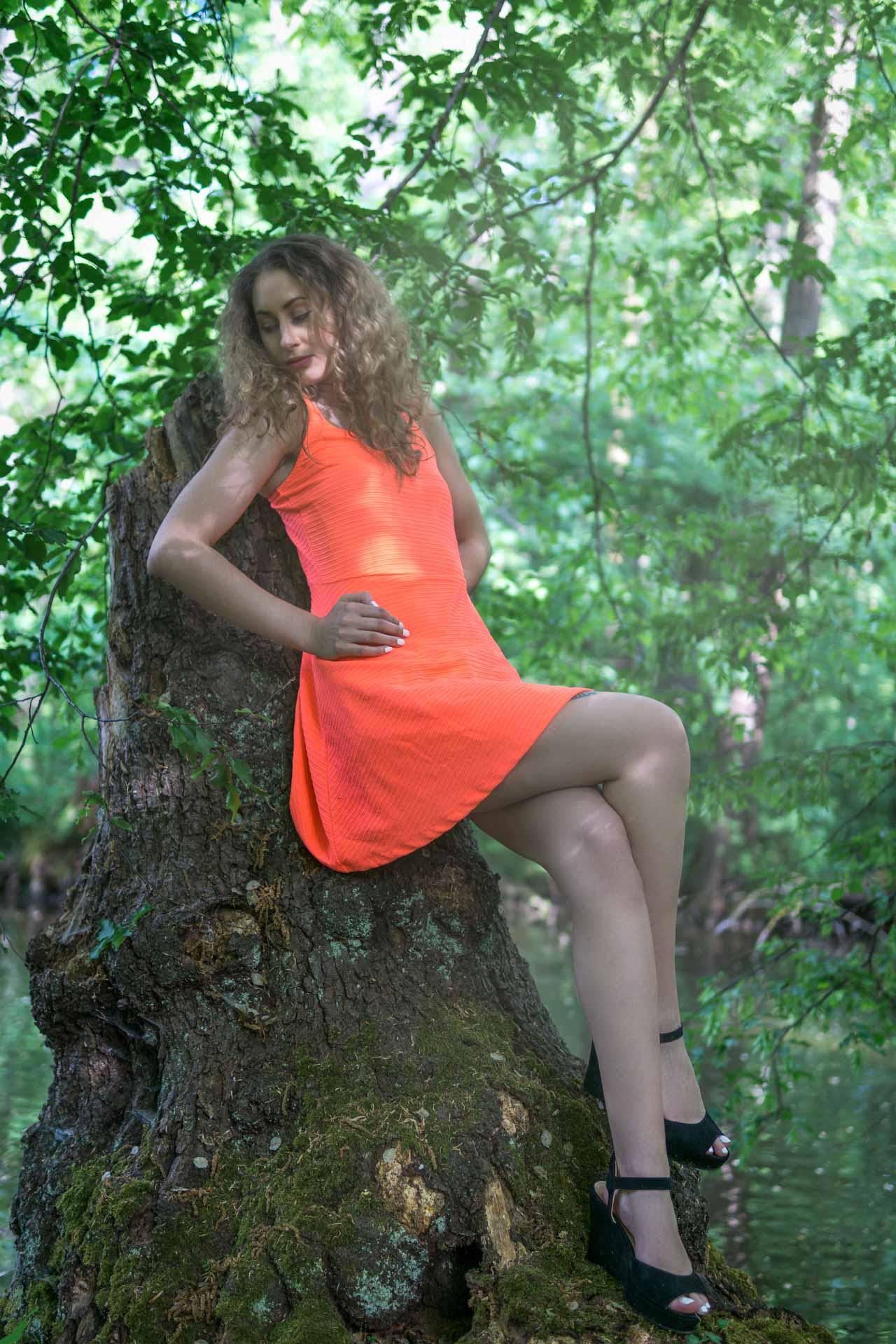 Laura an Baumstumpf angelehnt