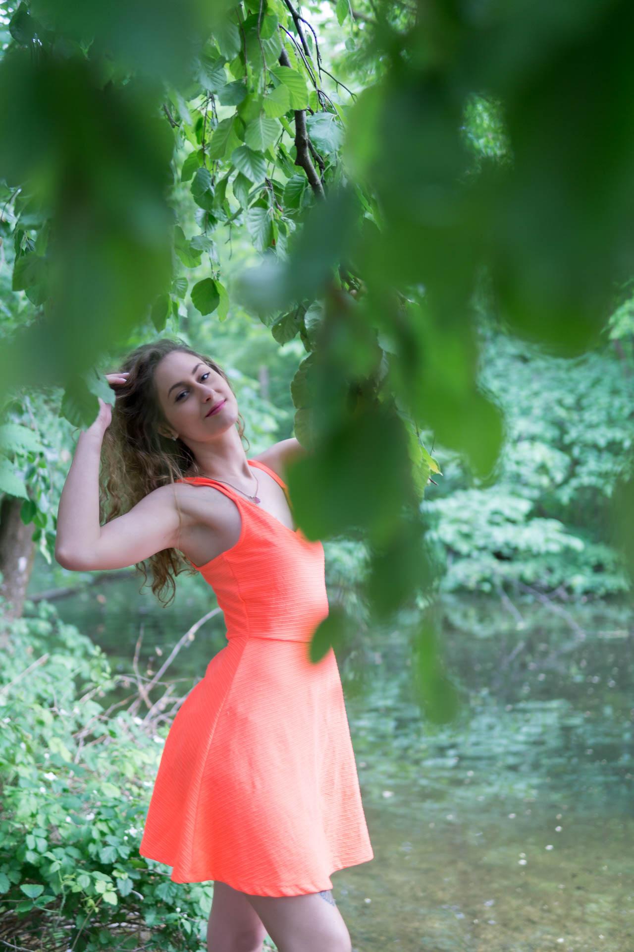 Laura sieht durch die Blätter des Baumes