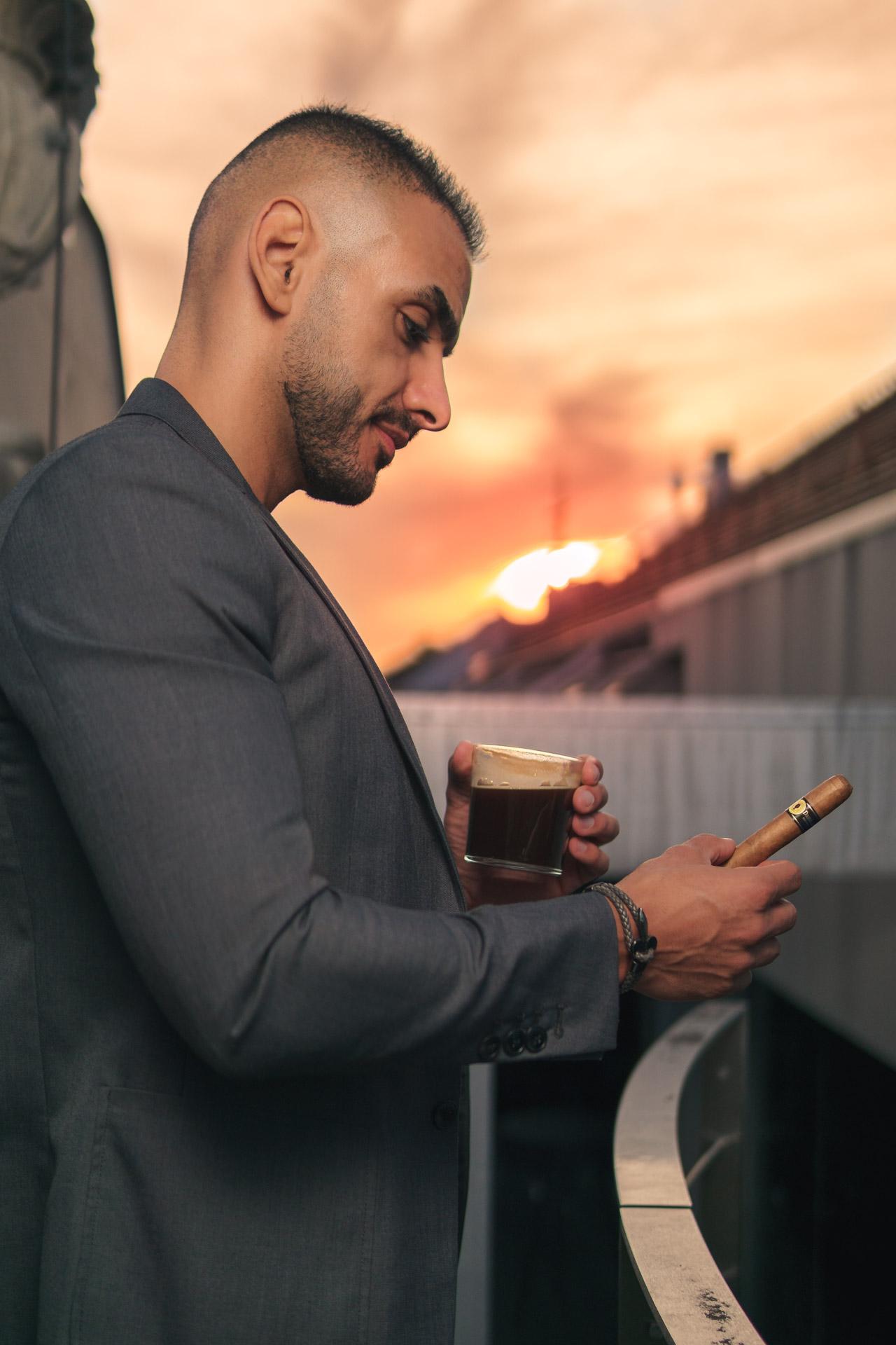 Enis steht mit Kaffee und Zigarre vorm Sonnenuntergang