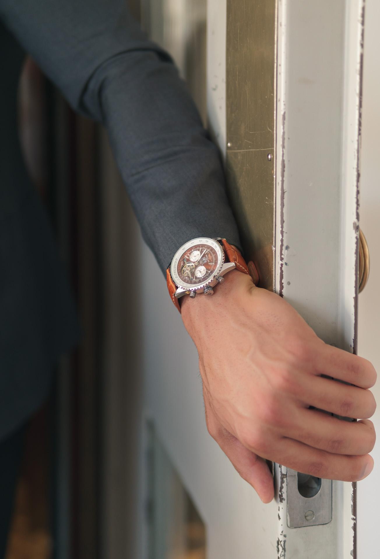 Arm öffnet Tür mit einer Rolex am Handgelenk