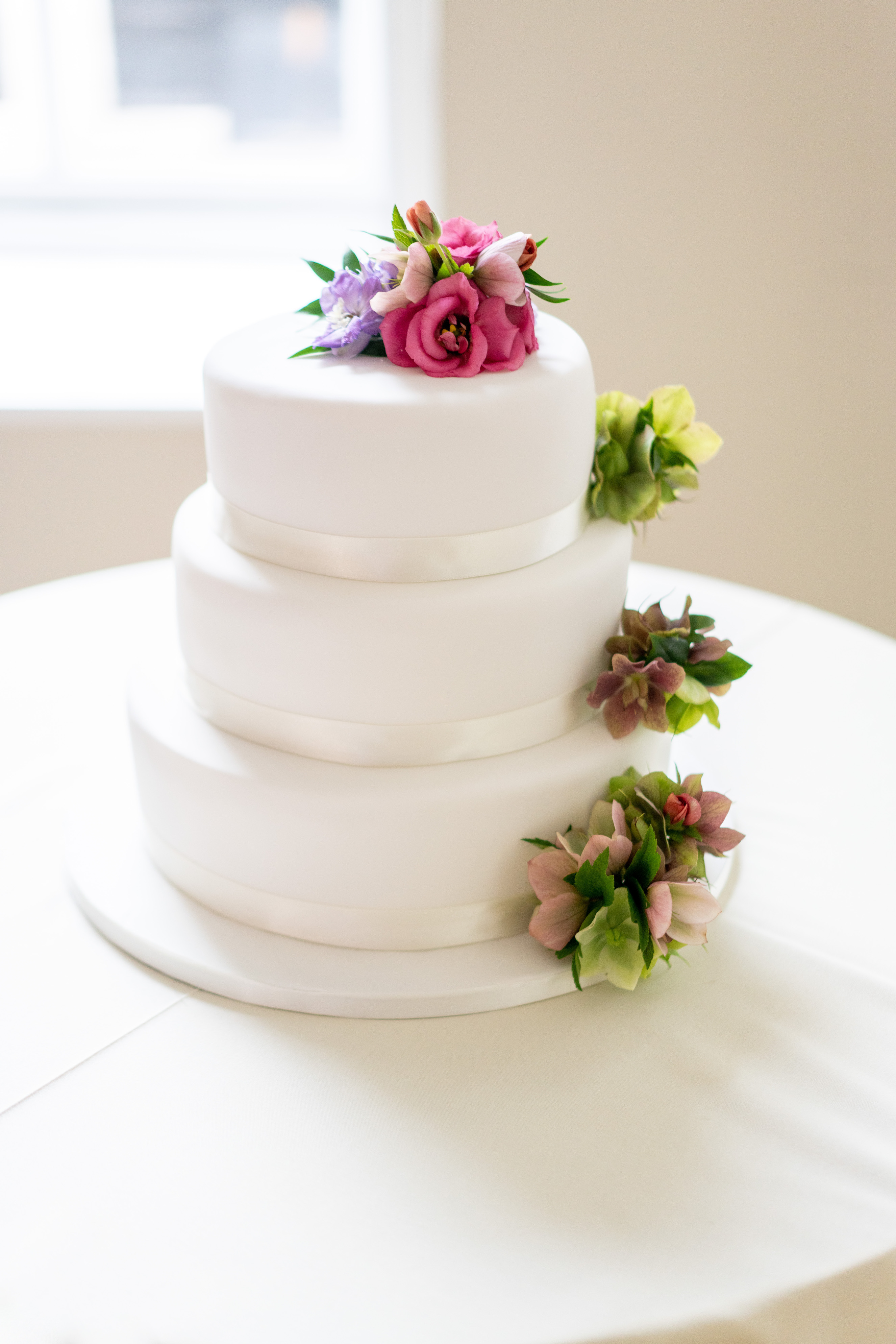 Subtle wedding cake decorations with pink eustomas and green hellebores