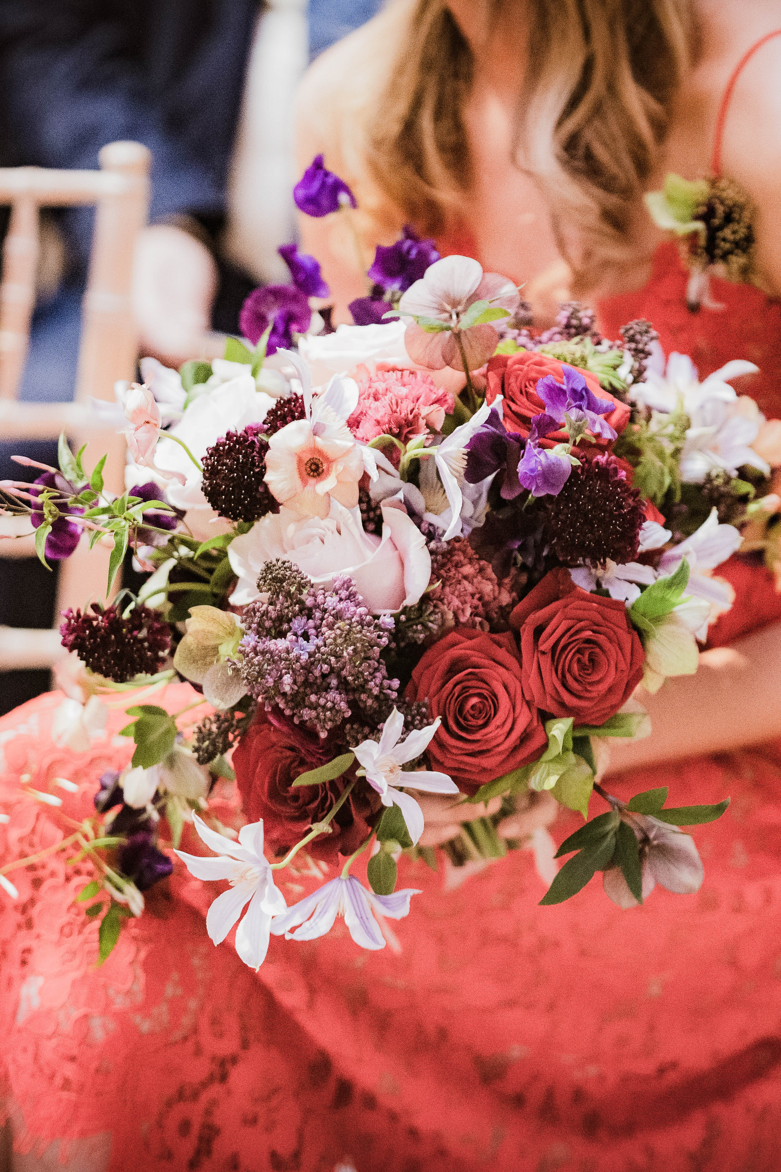 Bride in Red Dress Holding A Red Bouquet with Roses, Scabiosas, Lilac and Helleborus, Clematis, Butterfly Ranunculus