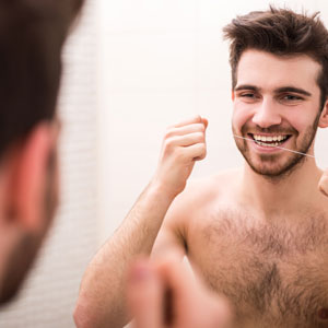 preventative dentistry man flossing teeth