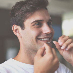 man flossing teeth to prevent gingivitis