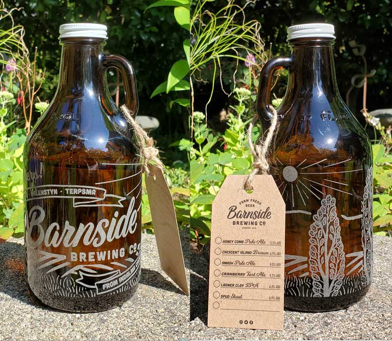 Photo of an engraved glass growler for Barnside Brewing as an opening gift. The growler sits in a sunny spot in a garden, and includes illustrated fields and trees in the design. The text on the Growler congratulates the four families who founded Barnside Brewing Co.