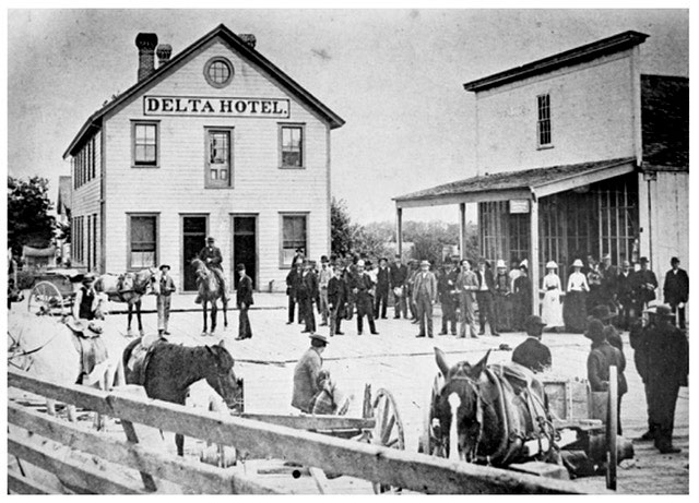 Archival image of the Landing Hotel in Ladner BC, from around 1911. THe grainy black and white photos shows buildings that have been illustrated on the can label.