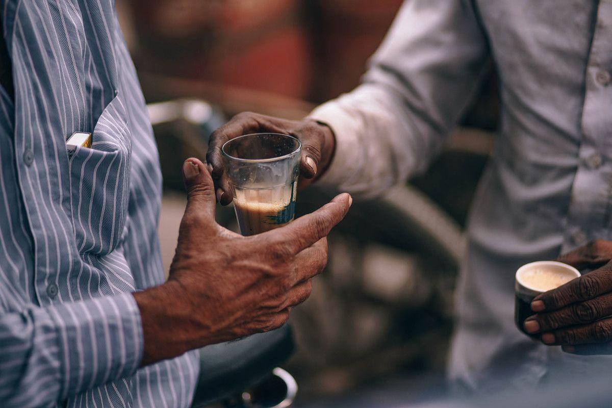 un hombre que le pasa a otro un vaso con té chai
