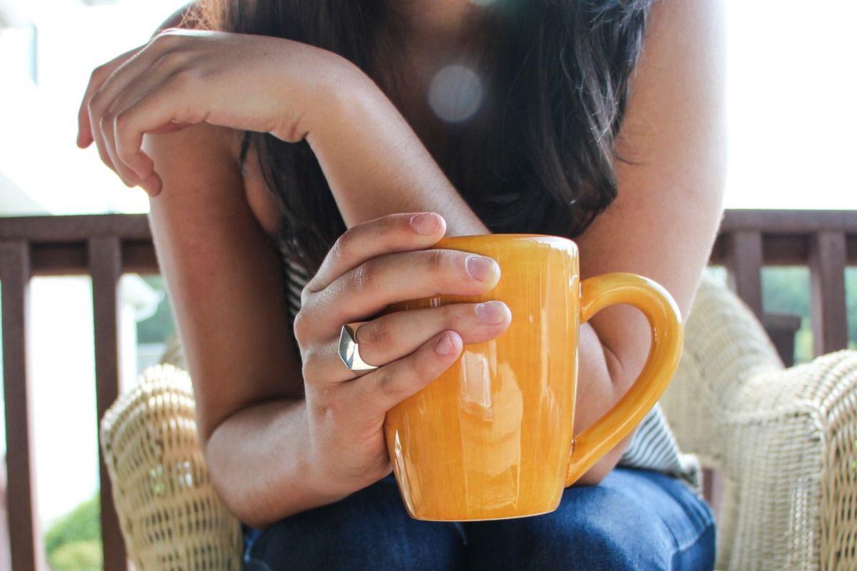 mujer relajándose con una taza amarilla