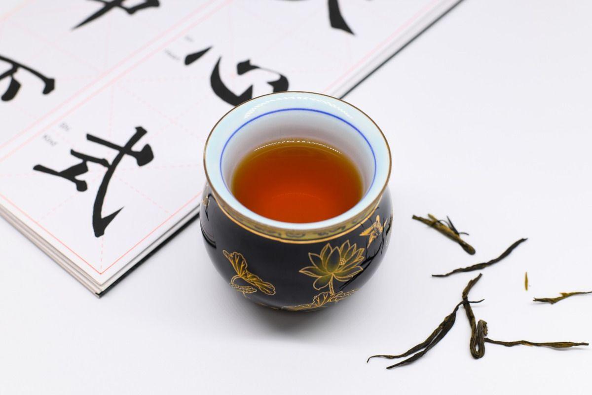 taza de té rojo y caracteres chinos al fondo