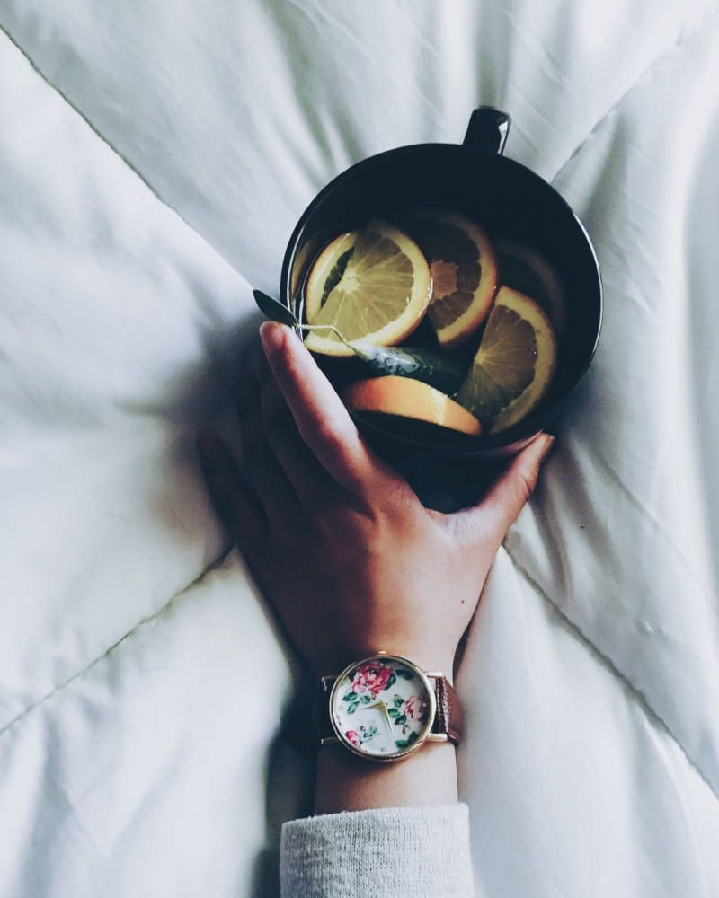 mano cogiendo una taza de té con limón
