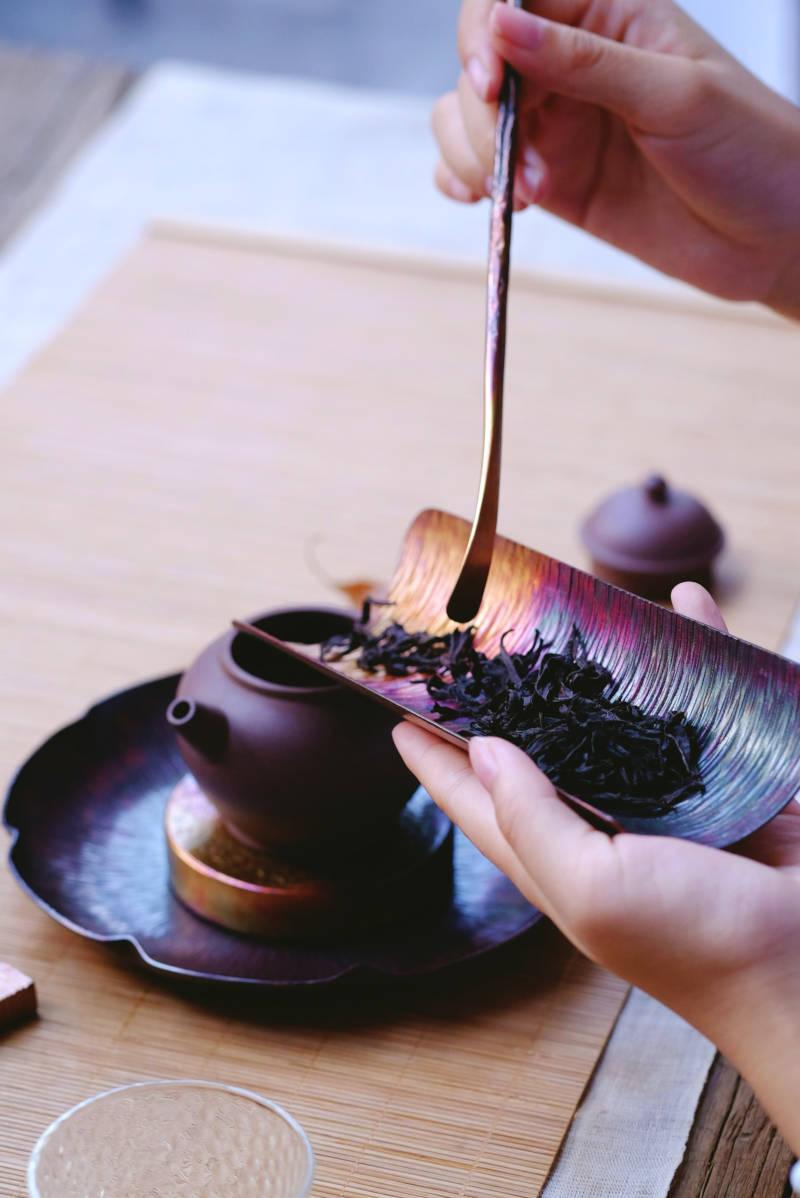 vertiendo té congou en una tetera
