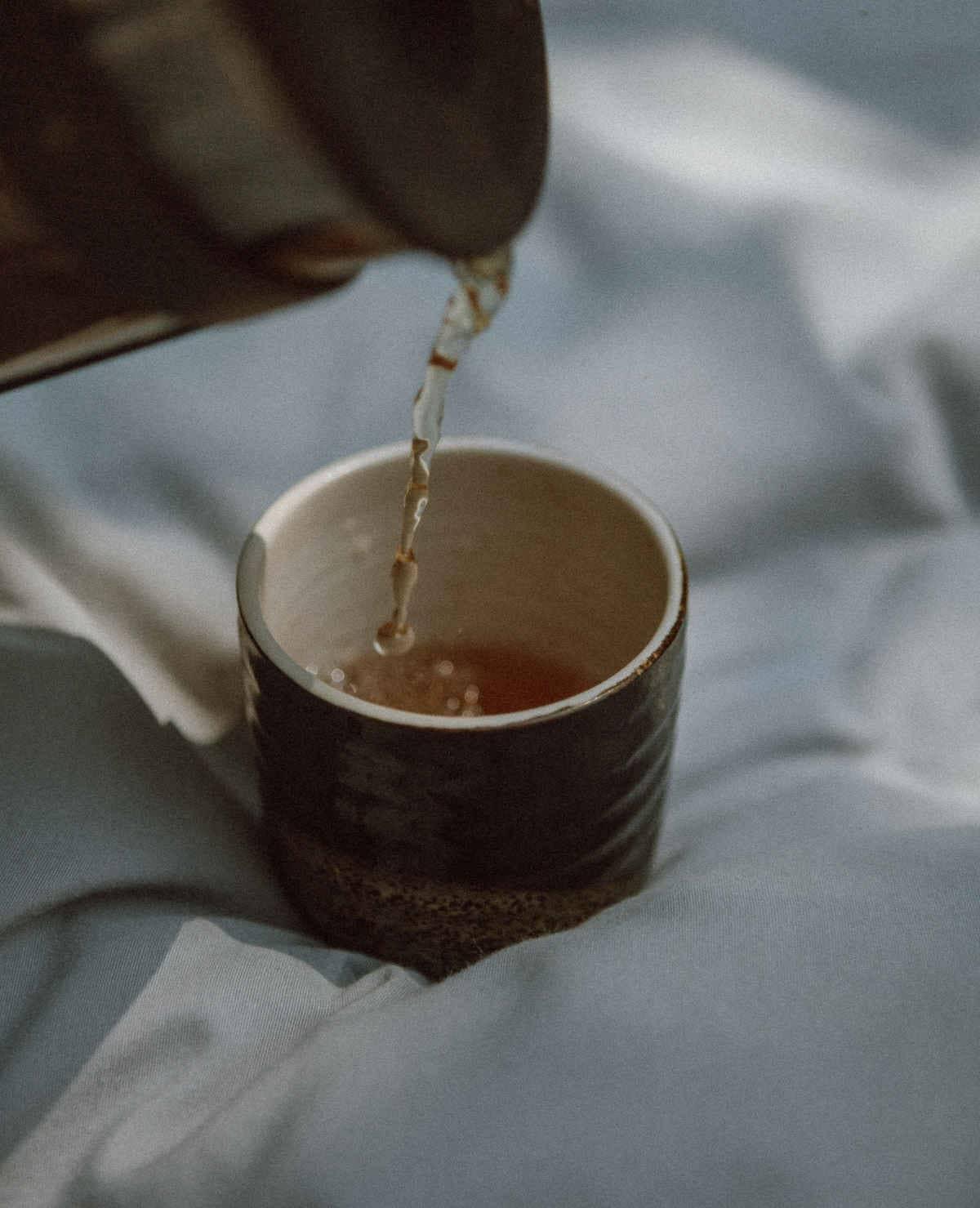 vertiendo té en una taza japonesa