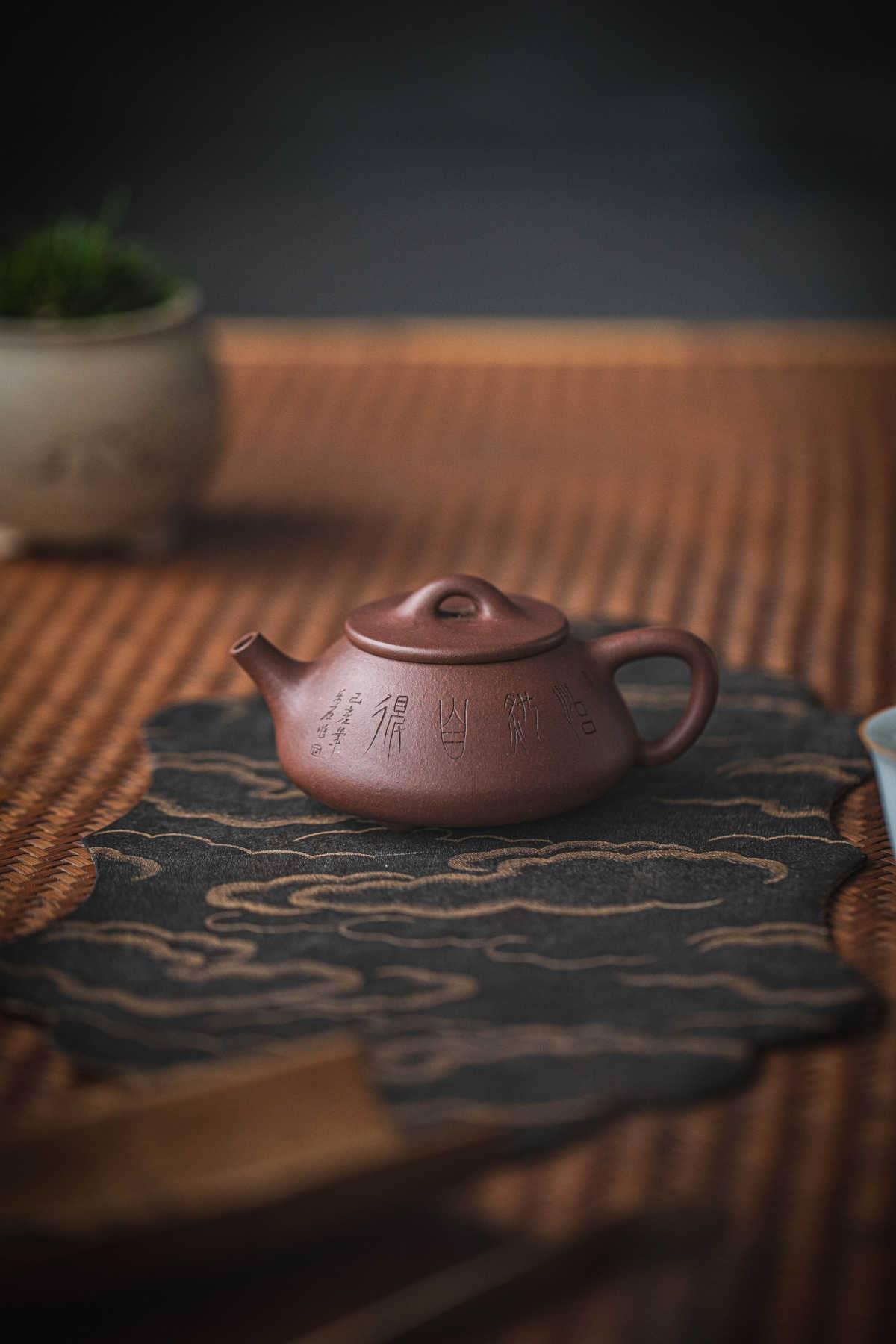 tetera roja china sobre mesa de bambú