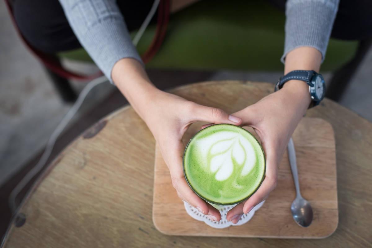 mujer sujetando una taza de matcha latte
