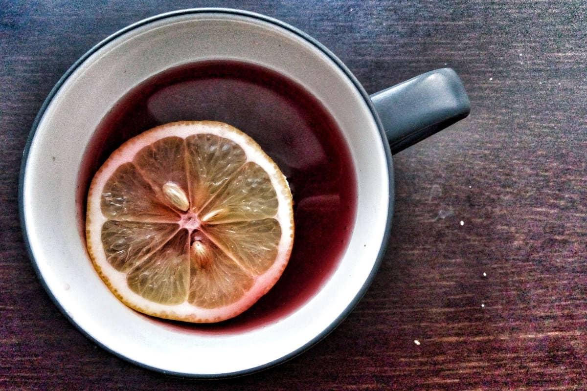taza de té de hibisco con una rodaja de limón