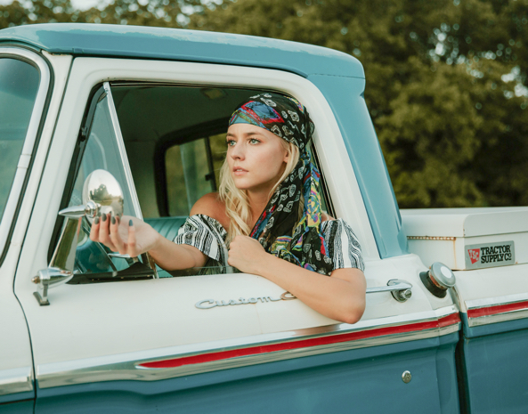 Žena v autě, která si upravuje zrcátko