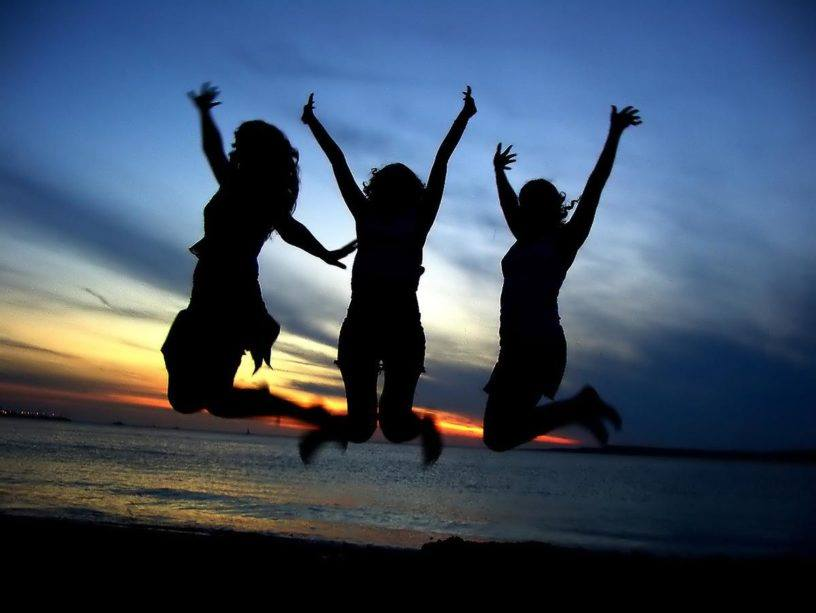 3 silhouettes jumping on a beach