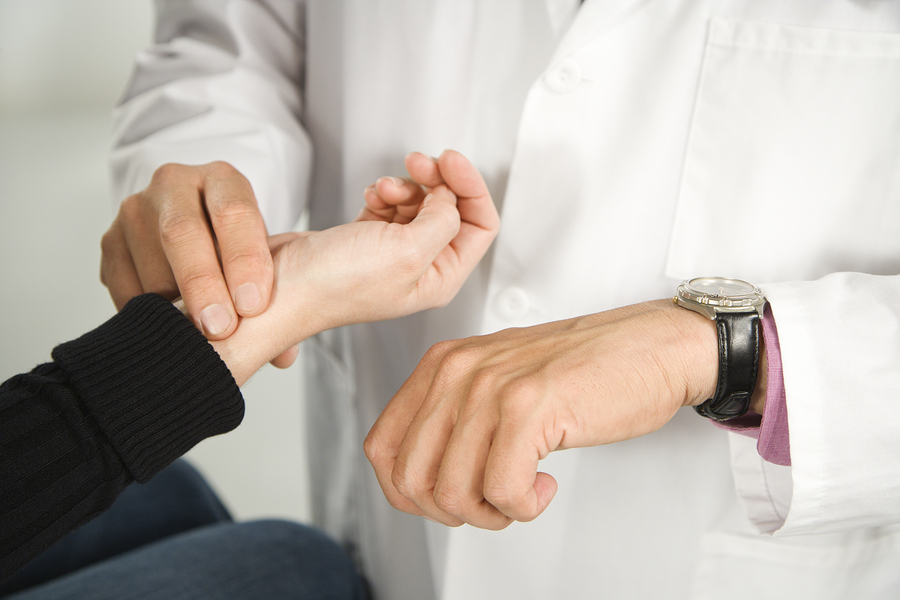 Physician checks patient's heart rate using watch and pulse from wrist.