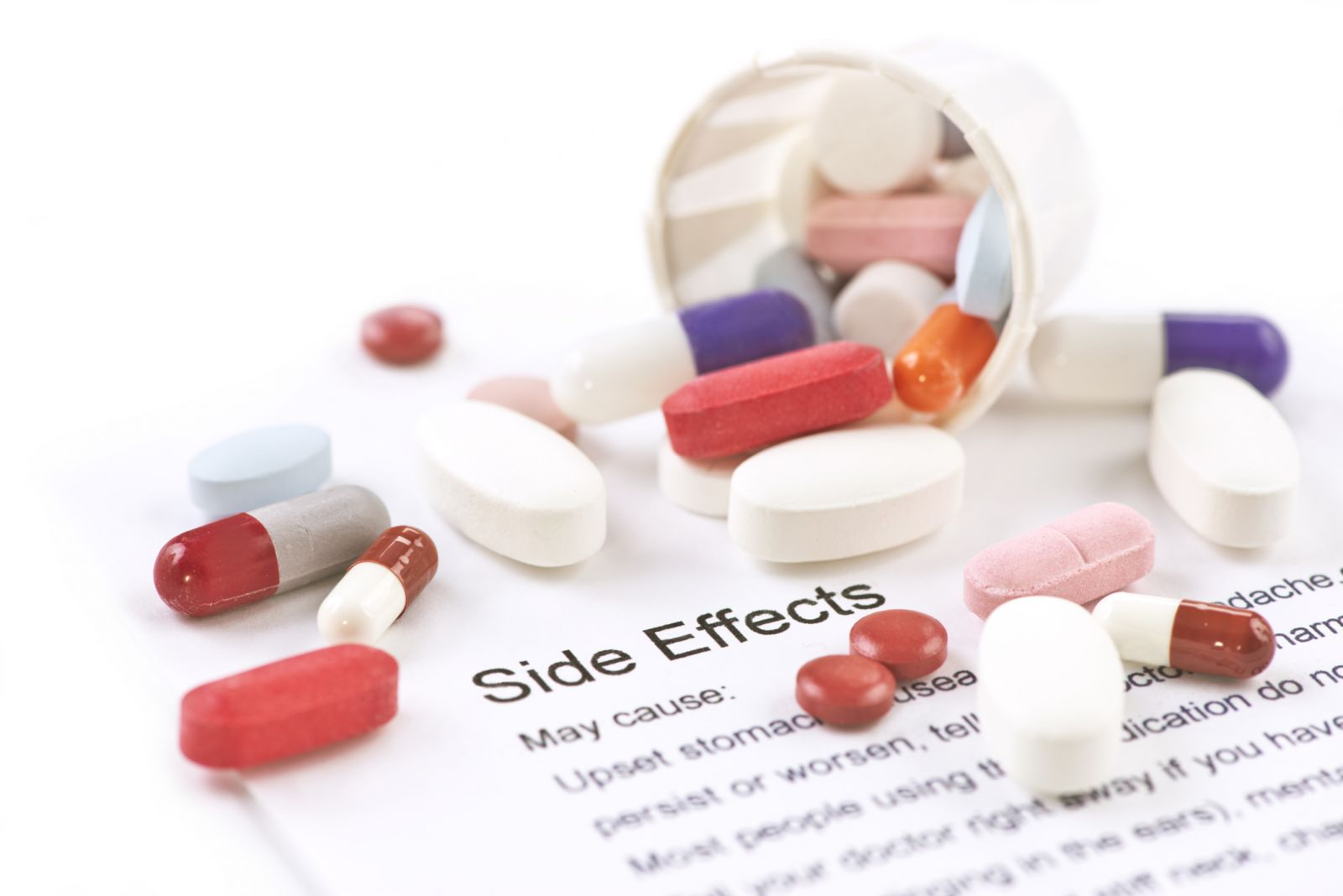 "Pills on top of a paper that reads ""side effects"""