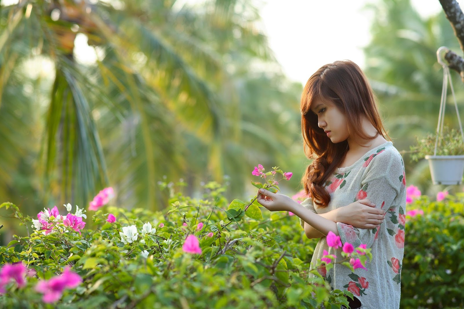 A sad woman looks down at a flower as she stands in a garden.