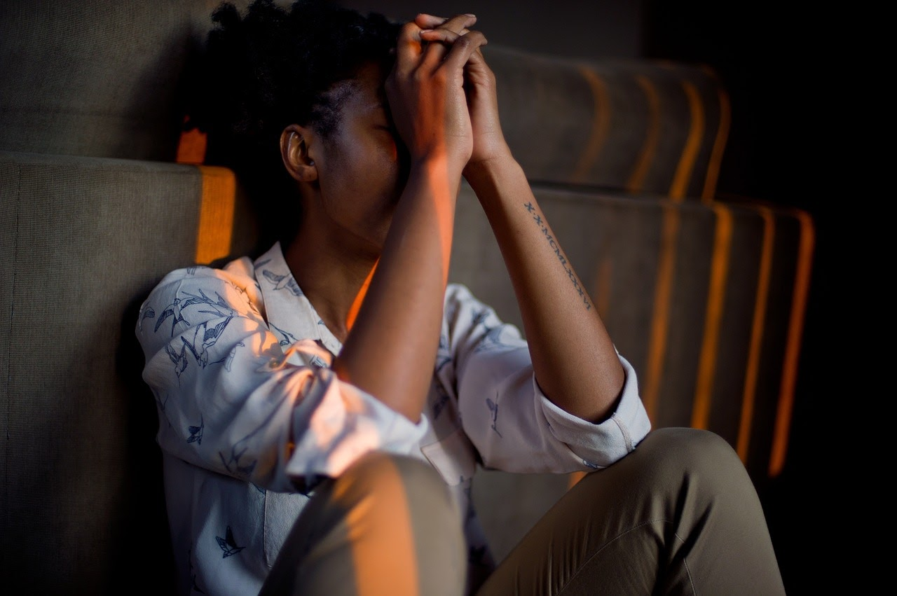 A woman sits with her hands over her face, appearing to be depressed and frustrated.
