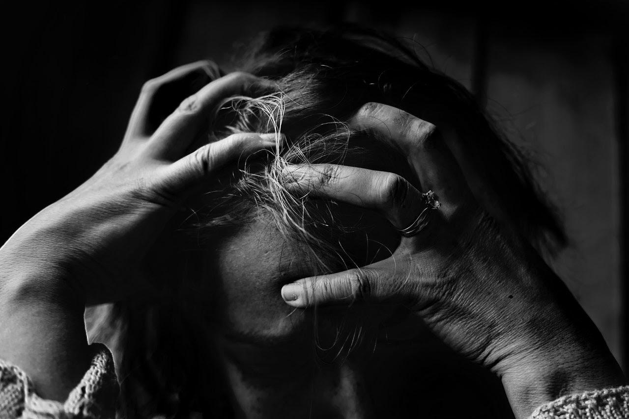 A woman is clenching her hands over her head, appearing to be distressed and upset.