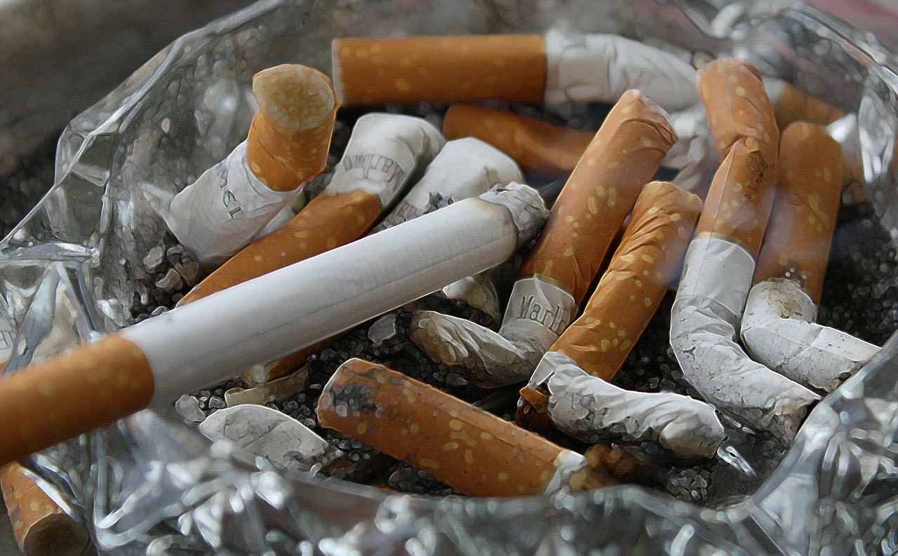 A pile of smoked cigarettes sit in an ash tray.